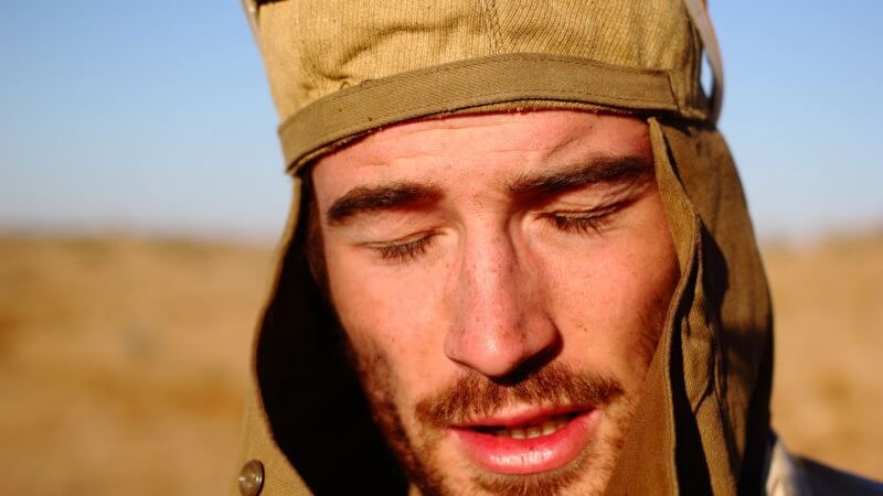Close portrait photo of exhausted desert runner with eyes closed.