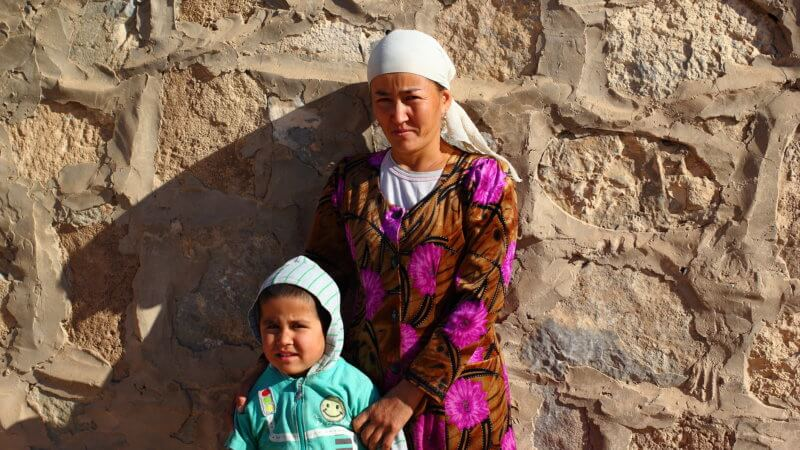 A woman and child pose outside their stone-built hut in the Kyzyl Kum.