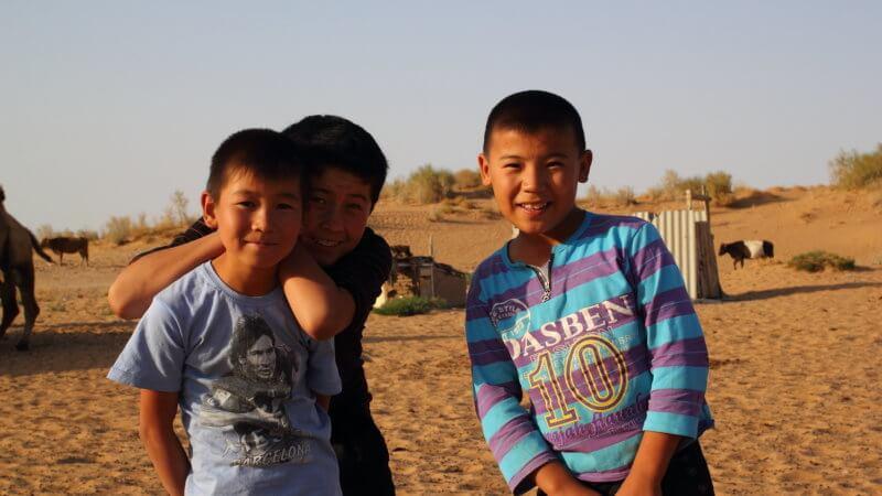 Three boys smiling for the camera in the Uzbek desert.