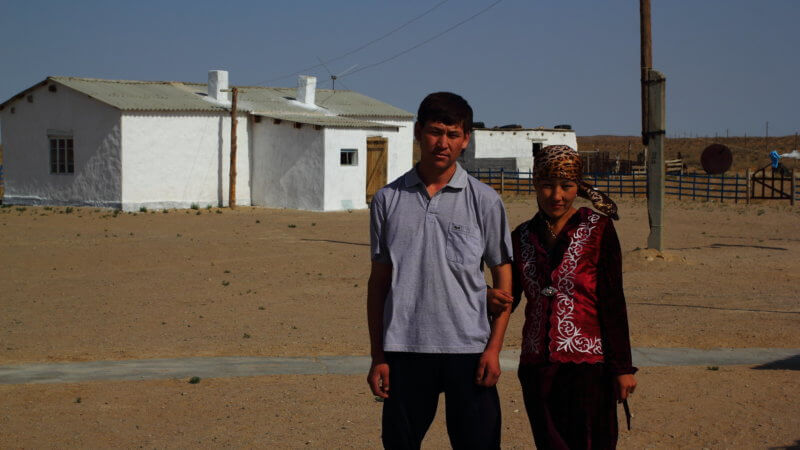 A Kazakh husband and wife pose for a photo outside their desert home.