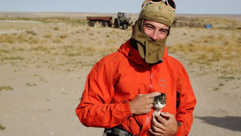 English runner, Jamie, pets a kitten that's poking out from his jacket pocket.