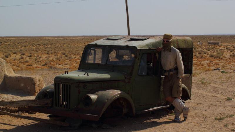 Desert runner leaning against an abandoned, green Soviet jeep.