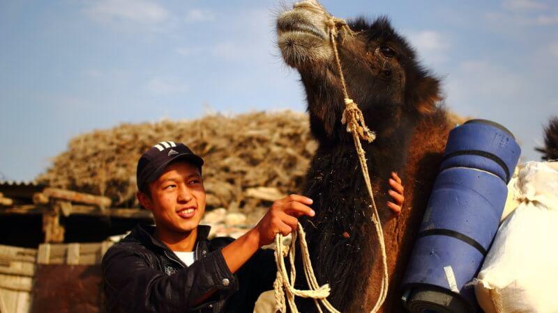 A teenage boy caresses the neck of a camel.