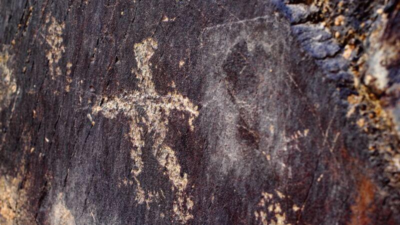 Close-up image of a petroglyph showing the faint outline of a stick-figure man.