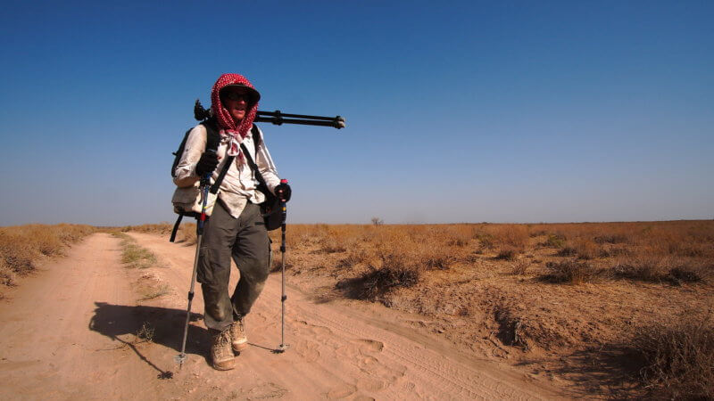 A cameraman walking in the desert on a sandy track, carrying equipment.