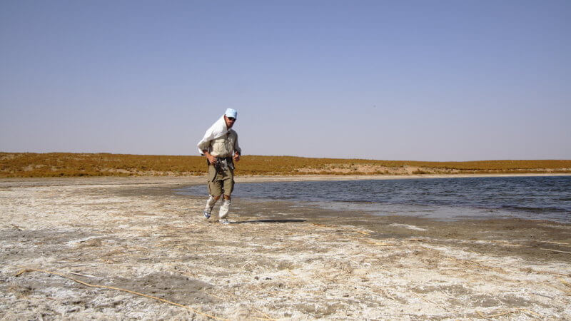 A desert runner running along the salty shores of Aydar Lake in Uzbekistan.