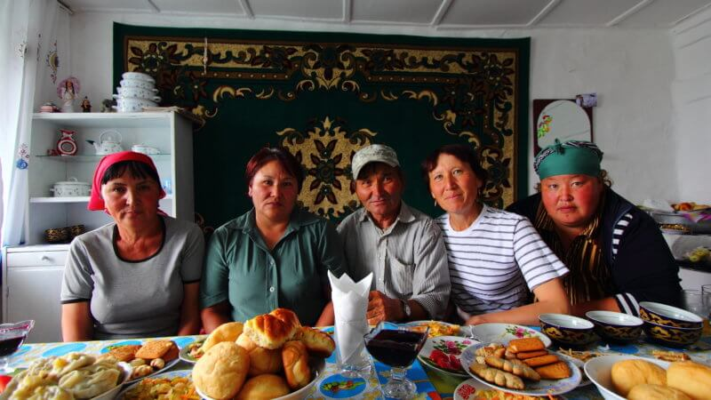 A family of five Kazakhs posing in front of a table of food.