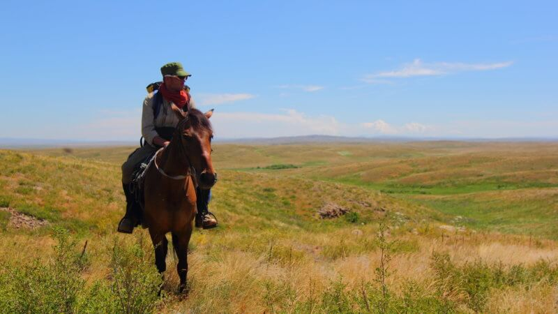 Man and horse ascending up a grass hill in Kazakhstan.
