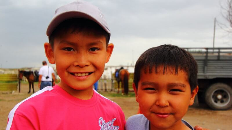 Two Kazakh boys smile for a photograph.
