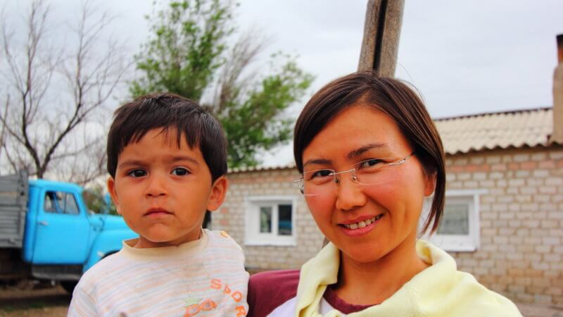 Kazakh woman with her son smiling.