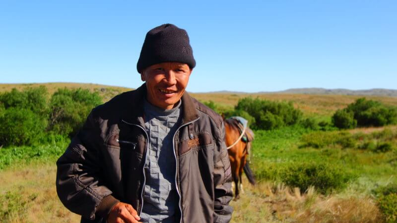 Kazakhstan horse man wearing a black beanie and jacket smiles.