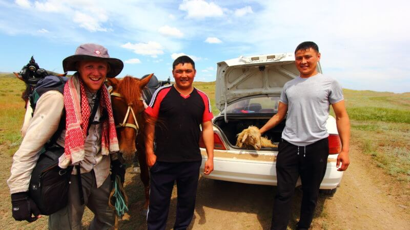 Two Kazakh men showing a goat they have in their car boot.