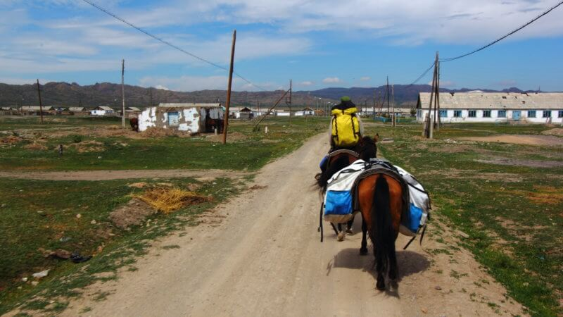 Backside shot of horse rider approaching a remote village in Kazakhstan.