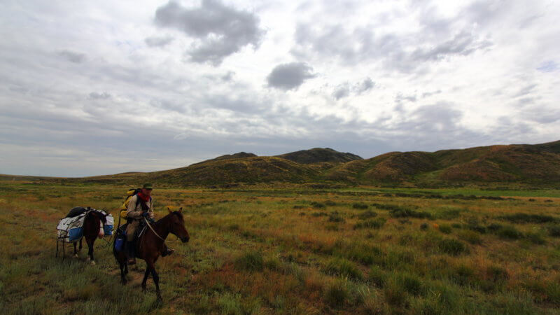 Horseman and rider travelling across a remote section of steppe in Kazakhstan.
