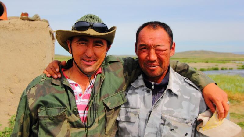 Two Kazakhstan men with arms over each other's shoulder. One has a big swollen eye!