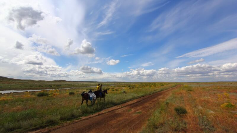 A horse rider with pack horse rides down a lonely dirt road in East Kazakhstan.