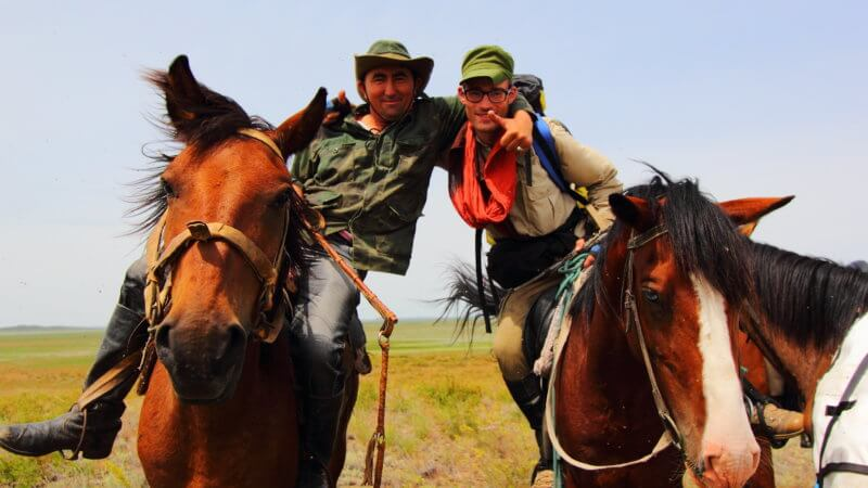Two riders sat on horseback with arms locked together smiling for the camera.