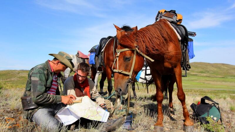Kazakhstan horse man reading a map with Jamie as one horse chews grass.