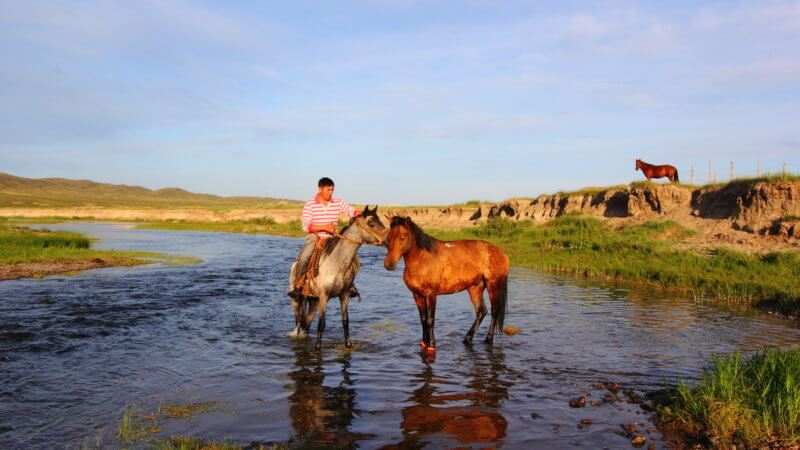 A Kazakhstan man sits on his horse in the river.