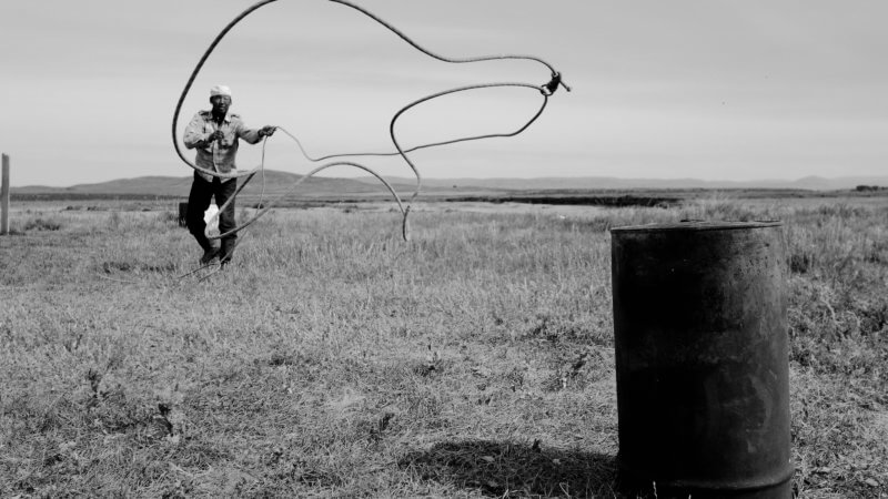 Black and white photo in Kazakhstan of man lassoing an oil drum for fun.