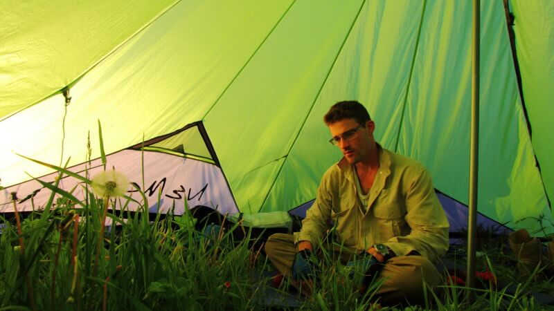 Jamie sat on the grass inside of a big floorless green tent.