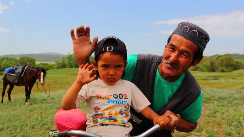 A Muslim Kazakhstan man and boy wave for the camera.
