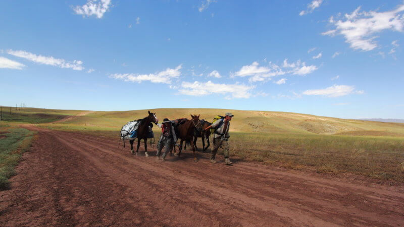 Wide shot of two men and three horses walking down a dirt road in Kazakhstan.