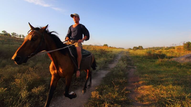 A rider gallops past the camera on horseback, riding barefoot.