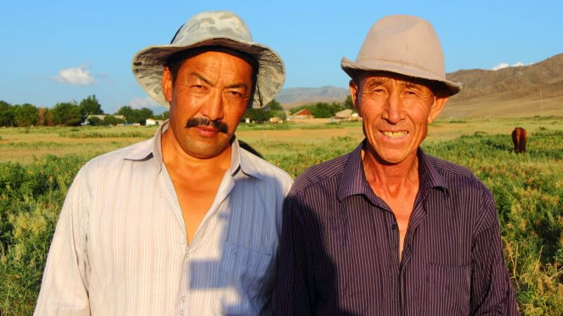 Two Kazakhstan men smile for the camera in the sunshine, wearing wide hats.