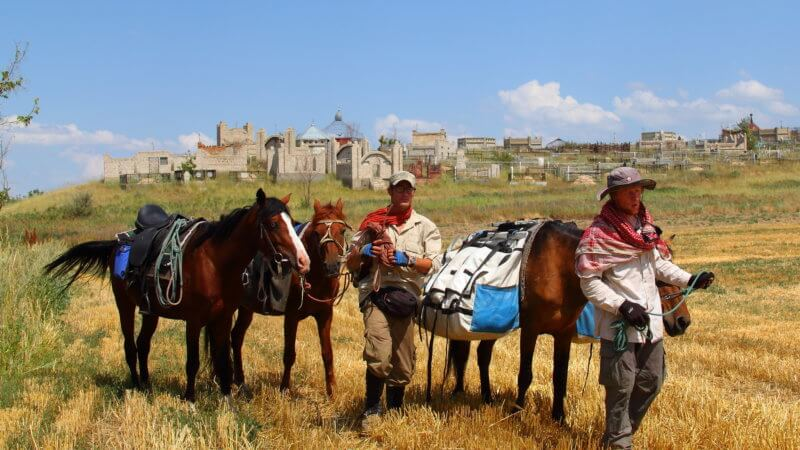 Two men with three horses next to a traditional Kazakhstan graveyard.