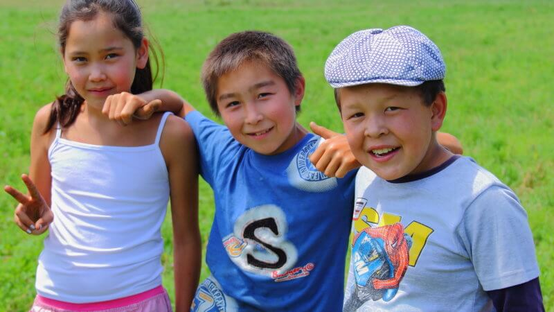 Three kids pose for a photo in East Kazakhstan, giving thumbs up and peace signs.