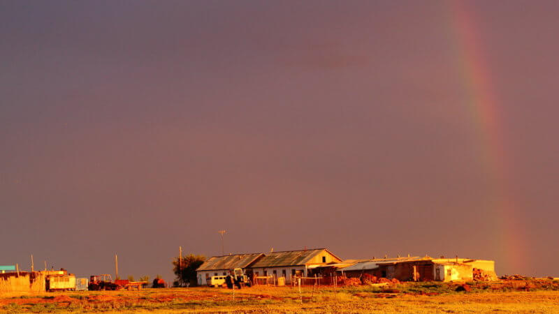 The faint rainbow ends on top of a sunset-soaked east Kazakhstan farmstead.