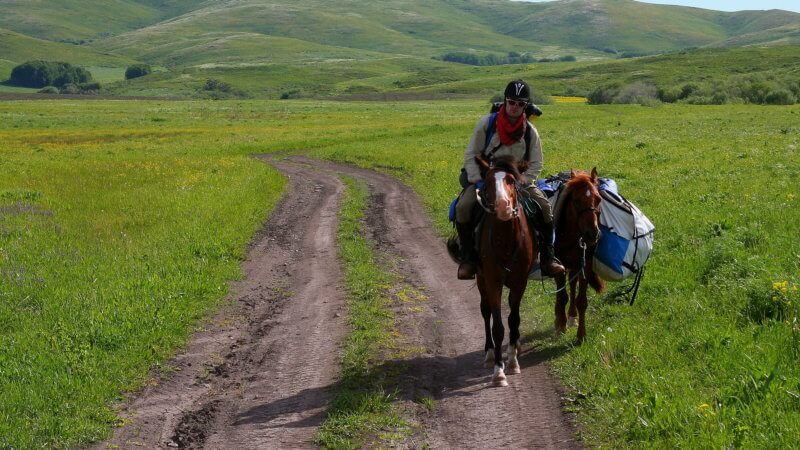 Jamie riding along a dirt track and green fields with two horses.