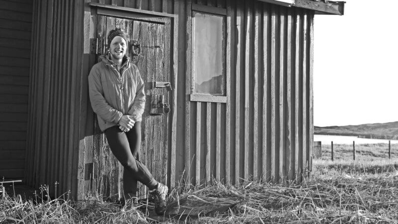 A black and white image of a man stood beside a Norwegian hut and smiling.