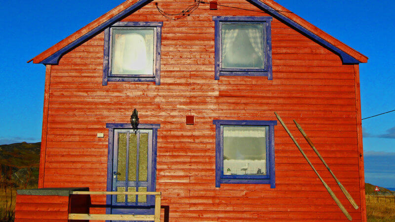 Frontside photo of a red house with blue window frames.