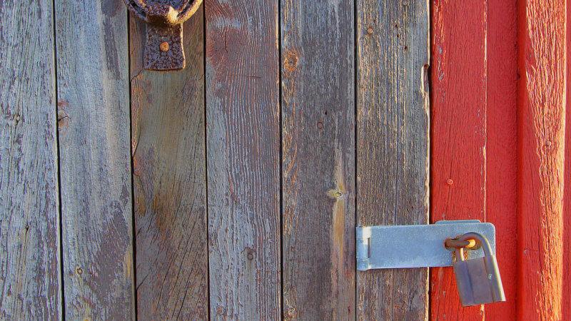 An old wooden door with two padlocks and a rusting door knocker.