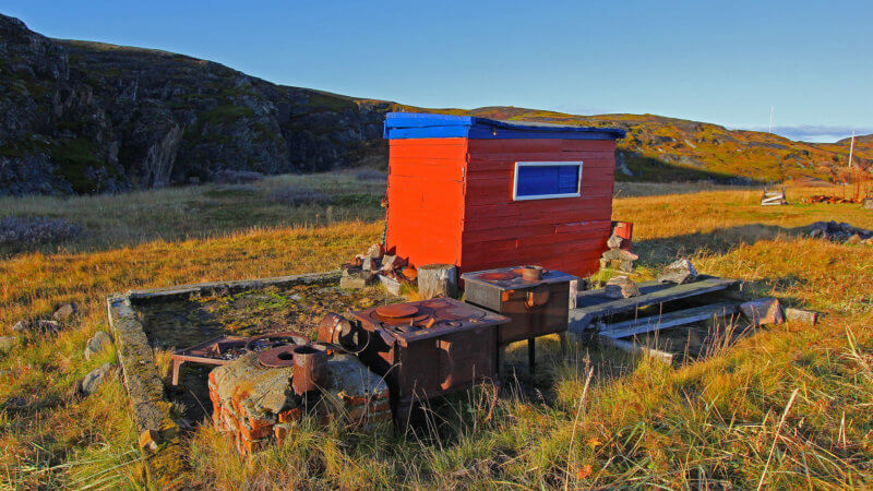 A tiny red hut and abandoned cookware left in the open Norwegian tundra.