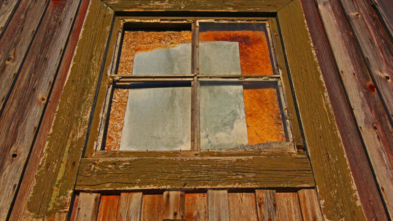Close-up of boarded-up window of an old Norwegian hut.