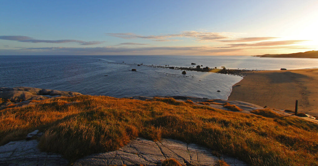 A line of tidal rocks, seen at sunset, disappears in to the Barents Sea.