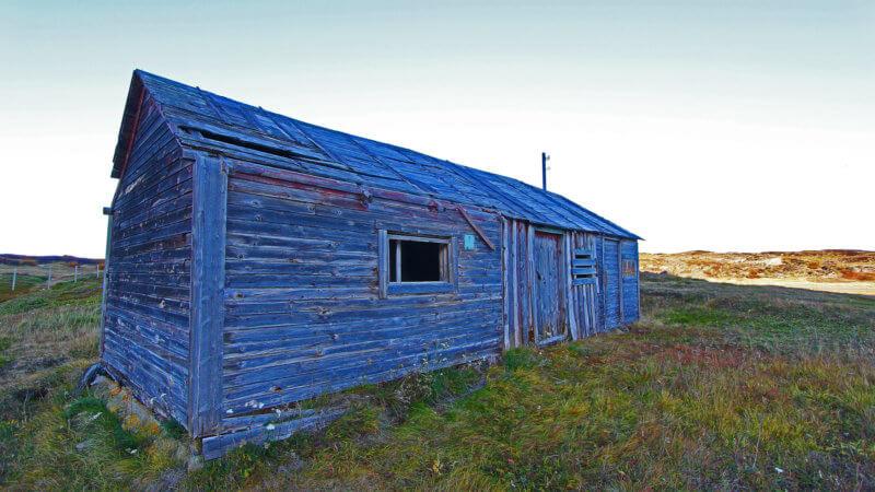 A mid-shot of an abandoned, wood-built fisherman's hut.