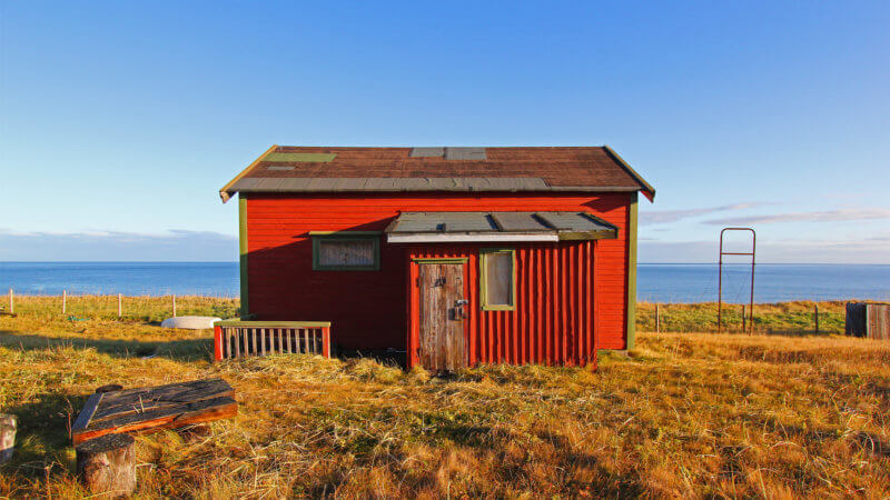 Frontside shot of an unused red house on the shores of the Arctic Ocean.