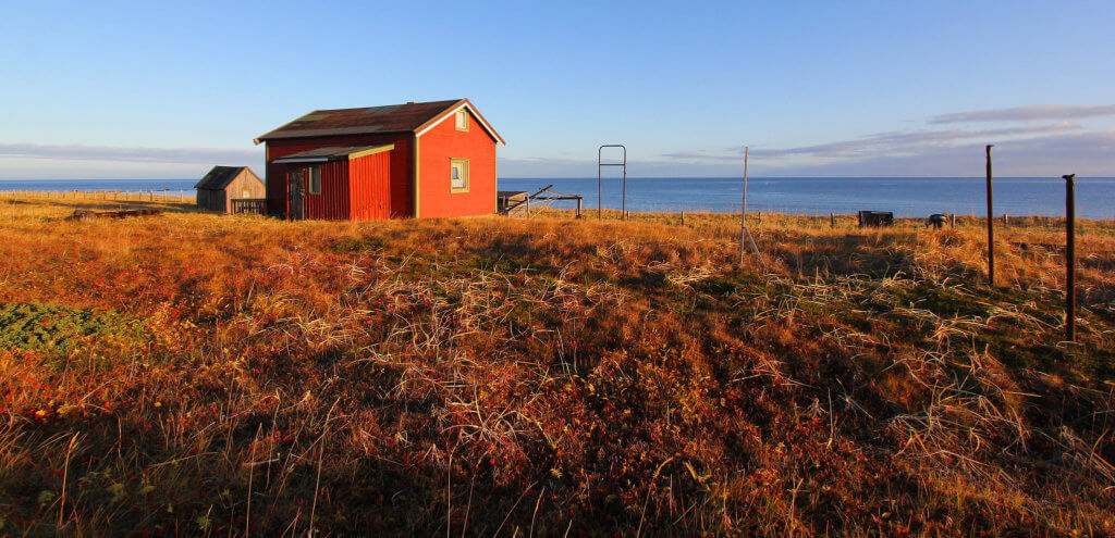 A red house stands alone on the sun-drenched tundra in northern Norway.