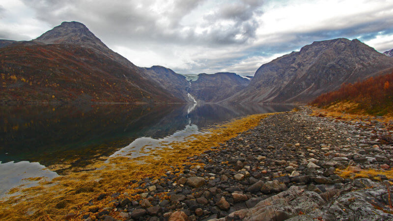 A quiet and isolated Norwegian fjord with a hanging valley and glacier in the distance.