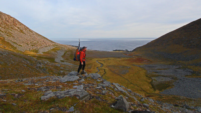 A man in the distance stood atop a rock overlooking a remote valley beside the Arctic Ocean.