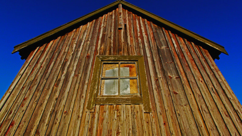 Frontside shot of a single boarded up window in a small wooden house.
