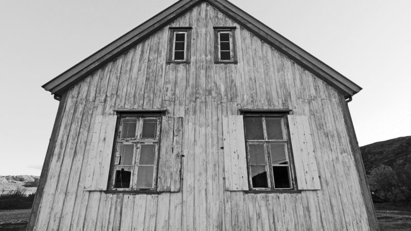 Black and white photo of the front of an abandoned house with four windows.