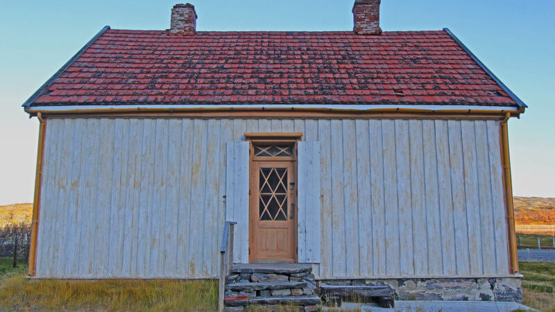 A frontside shot of a white shiplap constructed house, with a red roof and brown door.