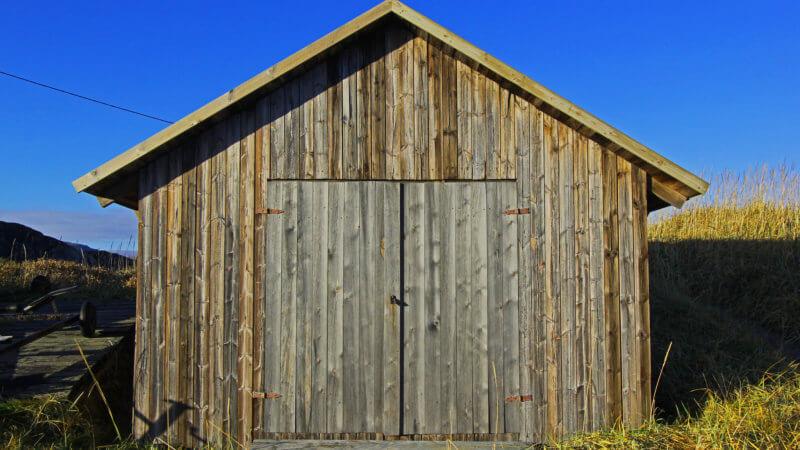 A frontside shot of a wooden boat storage hut in Grense Jakobselv.