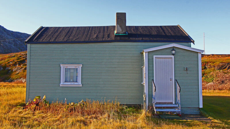 A small pastel green hut with a little window and white door in Grense Jakobselv.