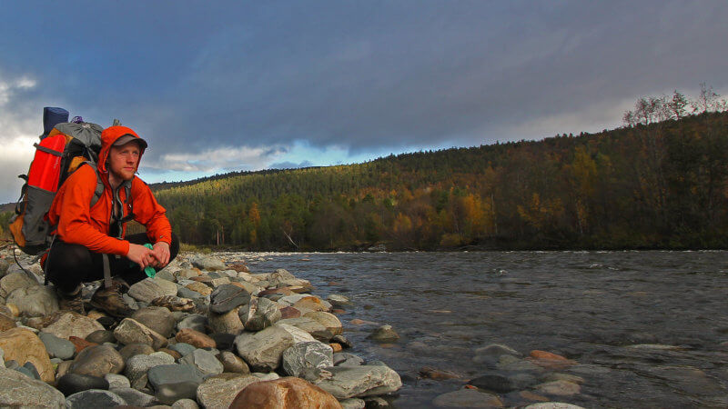 A man with a backpack crouched beside the shore of an Arctic Norway river.